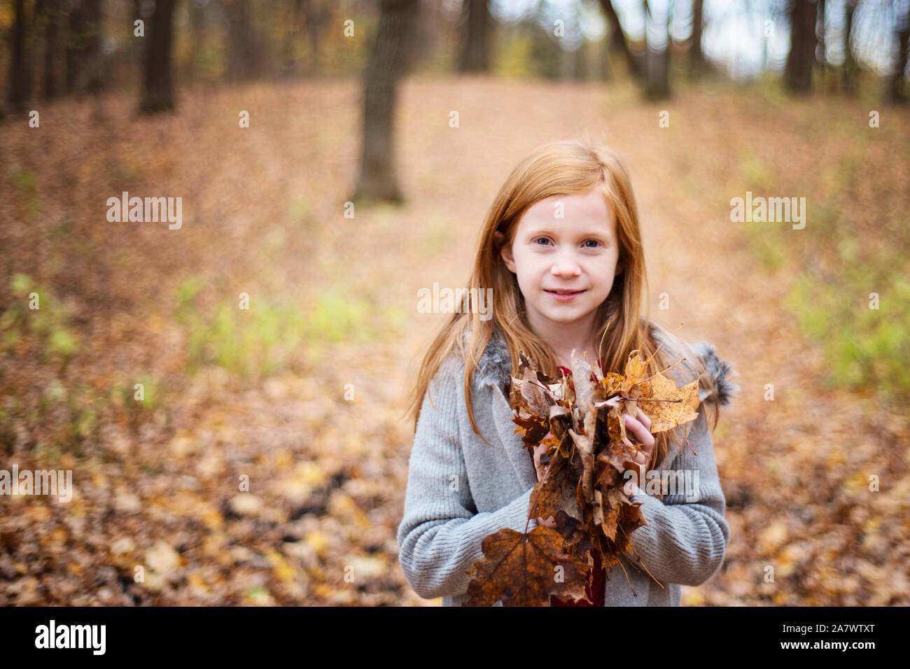 Young Red Hair Girl Playing Outside in Fall Leaves Stock Photo