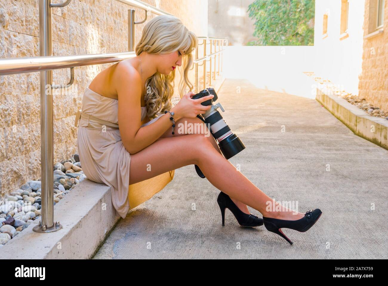Female model is looking down checking reviewing after photoshoot images photos on hand holding DSLR camera back lcd screen seated Stock Photo