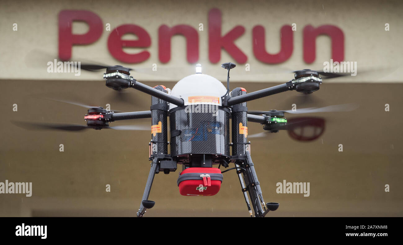 "Penkun, Germany. 04th Nov, 2019. A drone transports a defibrillator to the sky of Penkun. Defibrillators are small devices that can ""turn on"" the heart again with an electric shock in the event of cardiac arrest. A project team at Greifswald University Hospital is planning to fly defibrillators with drones to patients and medically trained first responders. The aim is to develop a system that deploys drones in such a way that they close the gaps in primary care in the countryside. In the district of Vorpommern-Greifswald a feasibility study is now starting. Credit: Stefa/dpa/Alamy Live News Stock Photo"