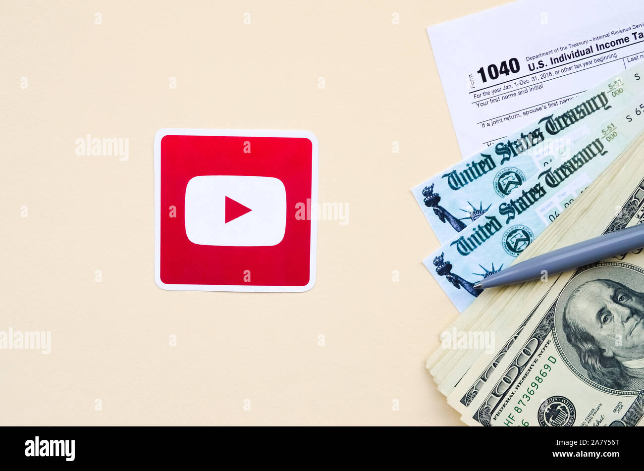 KHARKOV, UKRAINE - OCTOBER 3, 2019: Youtube printed logo lies with 1040 Individual Income tax return form with Refund Check and hundred dollar bills o Stock Photo