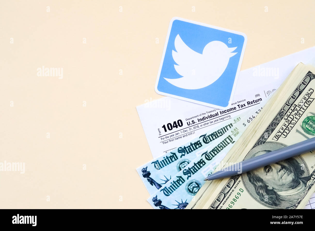 KHARKOV, UKRAINE - OCTOBER 3, 2019: Twitter printed logo lies with 1040 Individual Income tax return form with Refund Check and hundred dollar bills o Stock Photo