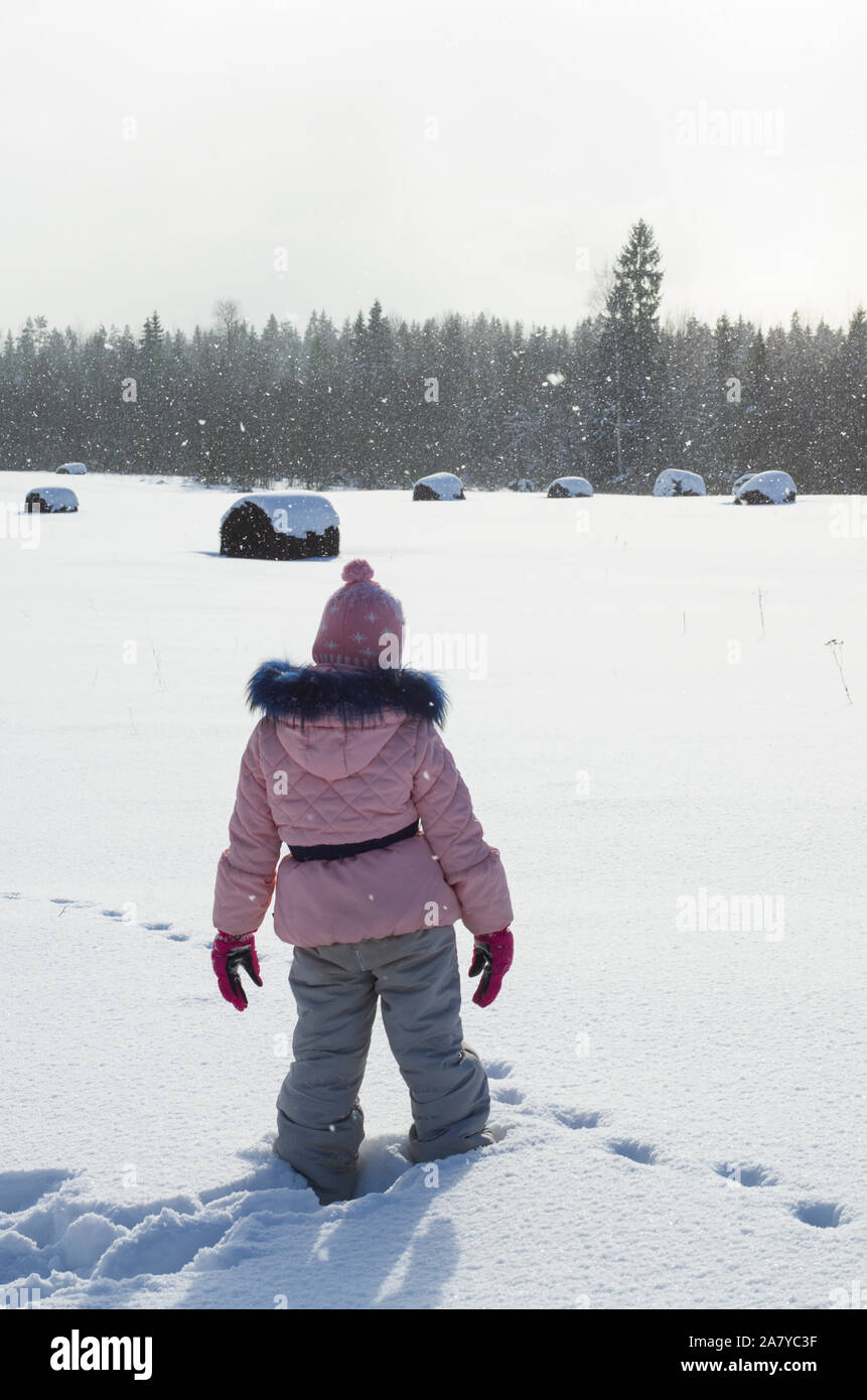 Winter scene with a little girl on a snow field during a light snowfall vertical orientation Stock Photo