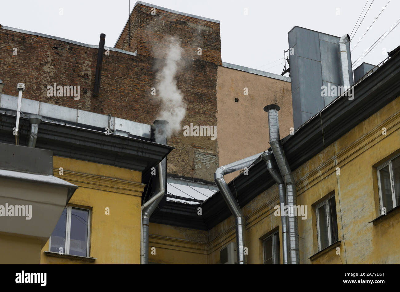 Walls of old houses with silvery pipes ventilation system with smoke over one of the pipes Stock Photo