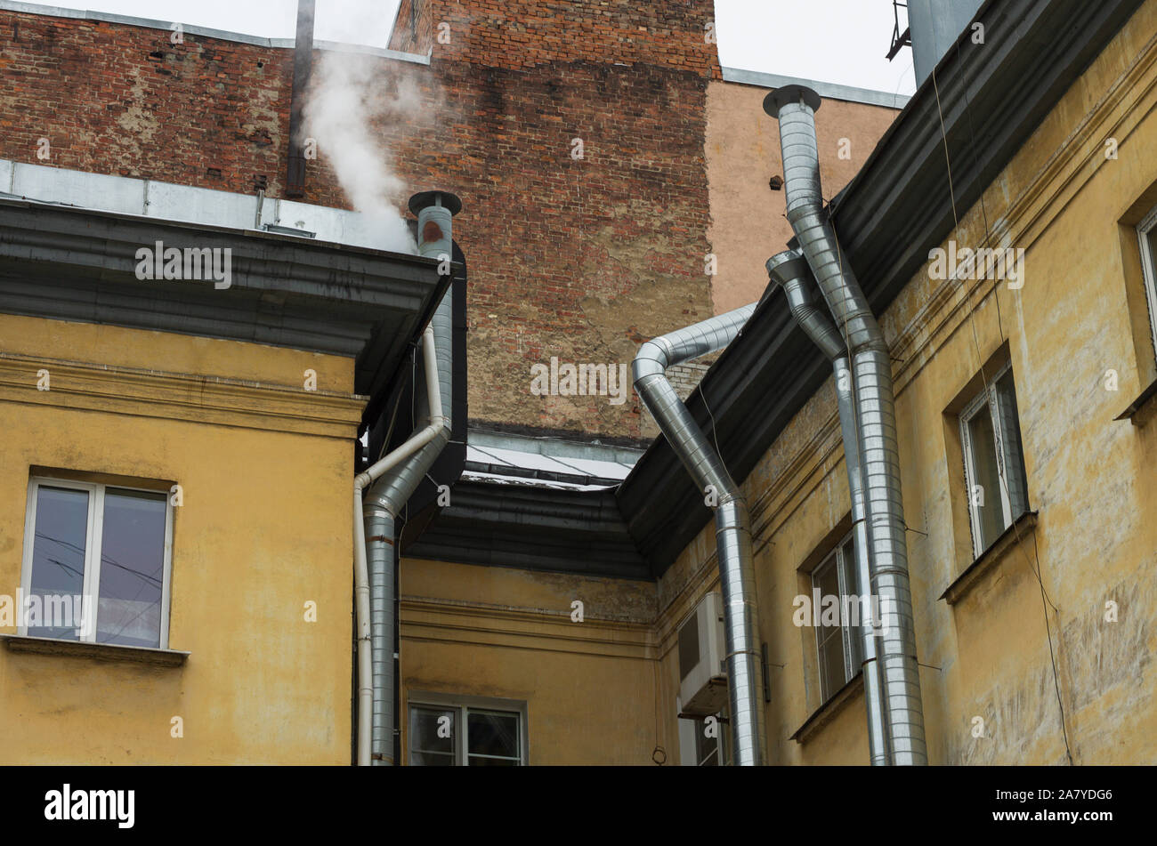 Yellow wall of old house with shiny silvery pipes ventilation system Stock Photo