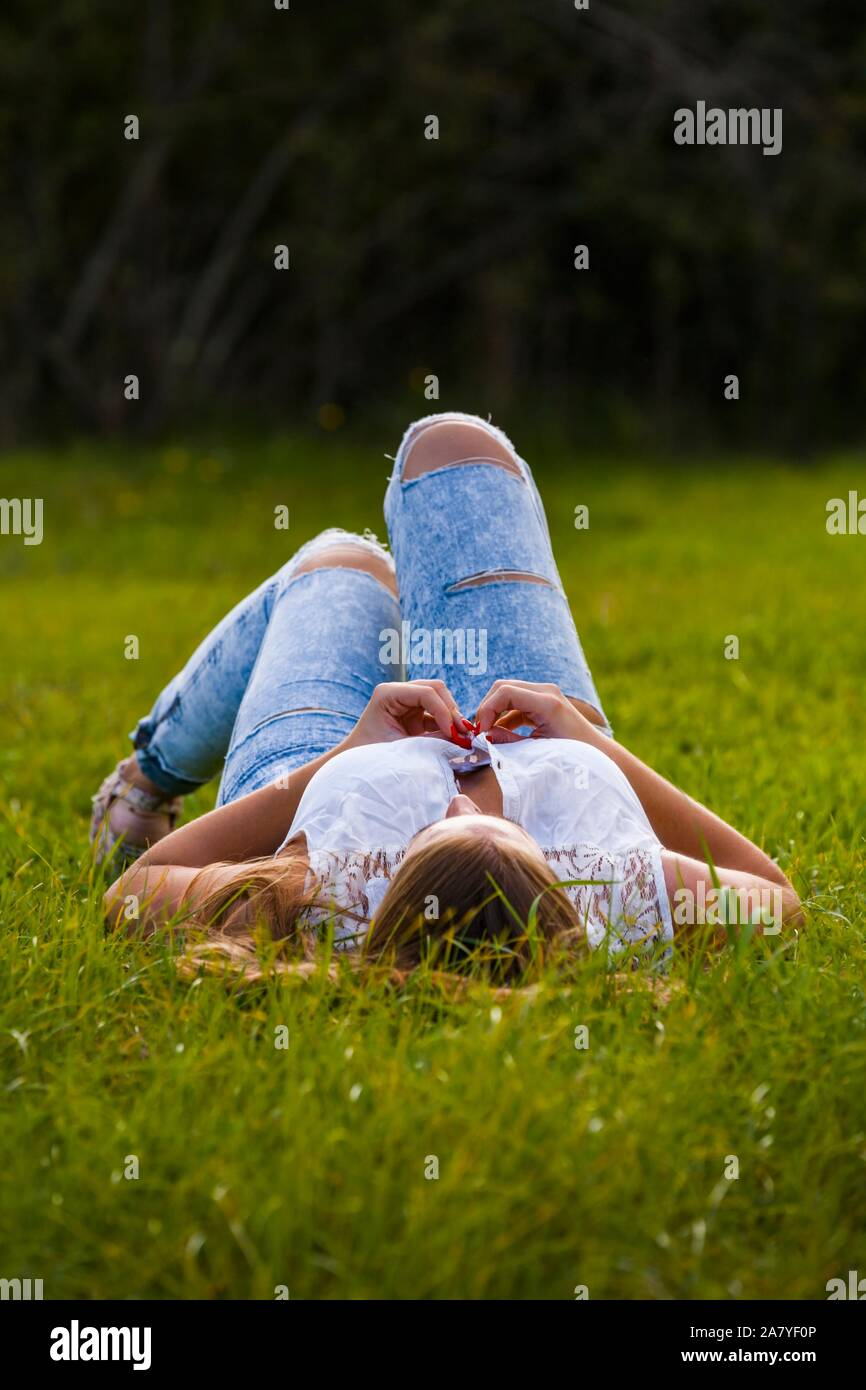 Big breasts aka boobs hand hands button buttoning shirt buttons young woman is lying on her back on greenfield on country-side countryside Stock Photo