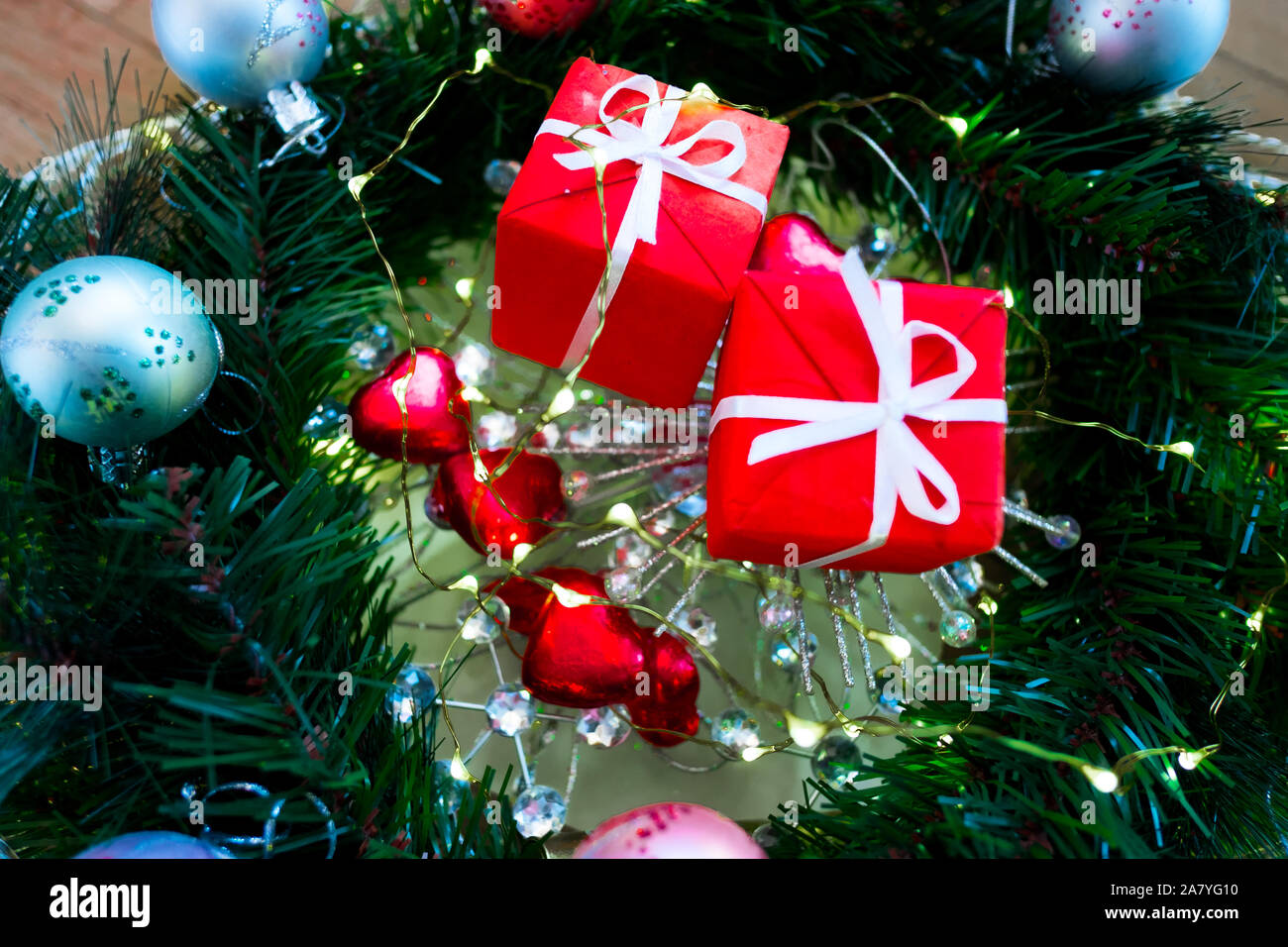 Decorated Christmas Tree Closeup With Red Christmas Gifts With White Ribbon Heart Shaped Sweets And A Lot Of Lights Glitter And Blurred Bokeh Stock Photo Alamy