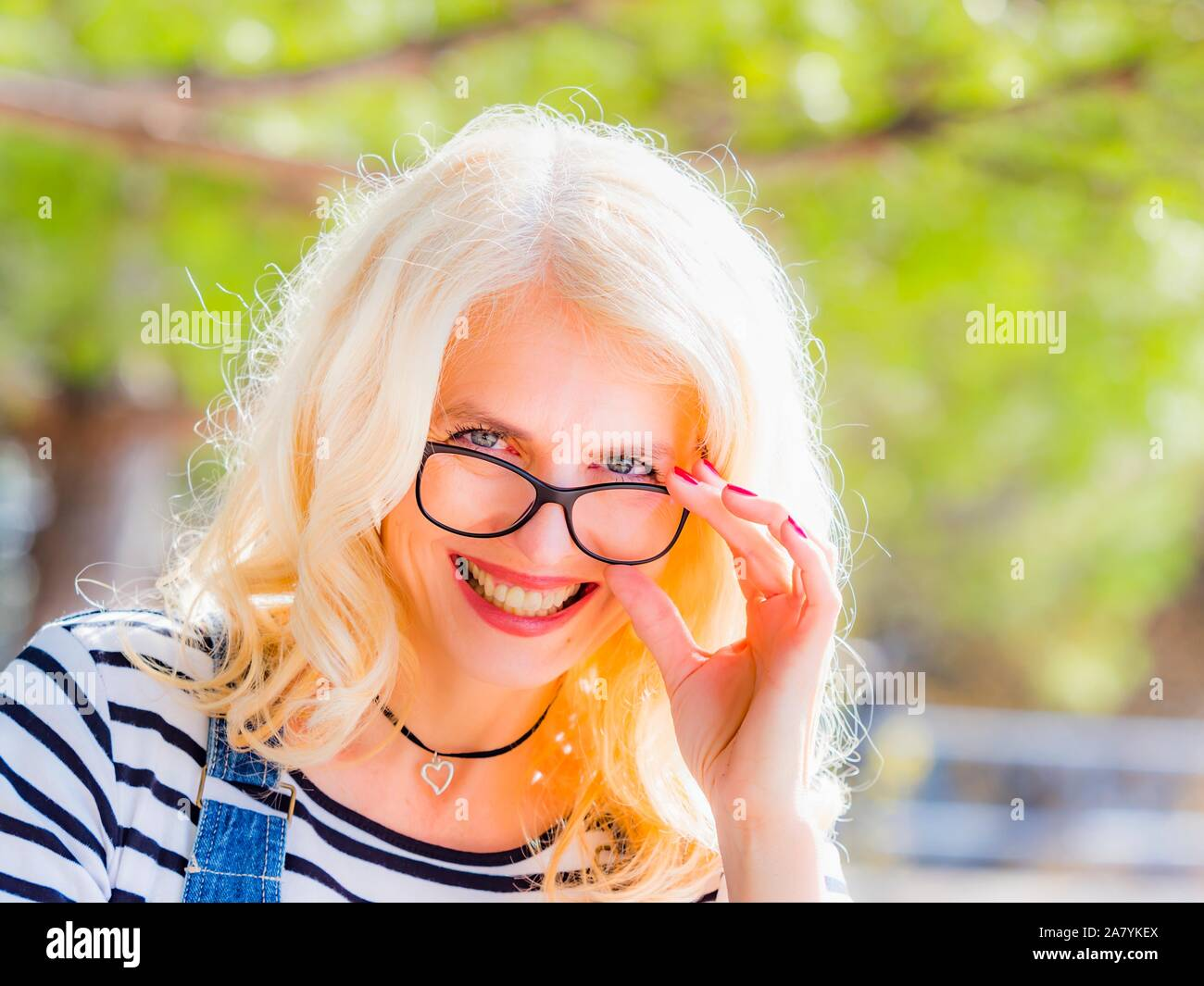 Backlighted portrait headhot eyeshot beautiful mid-adult woman in nature very happy smiling at camera peeking over spectacles Stock Photo