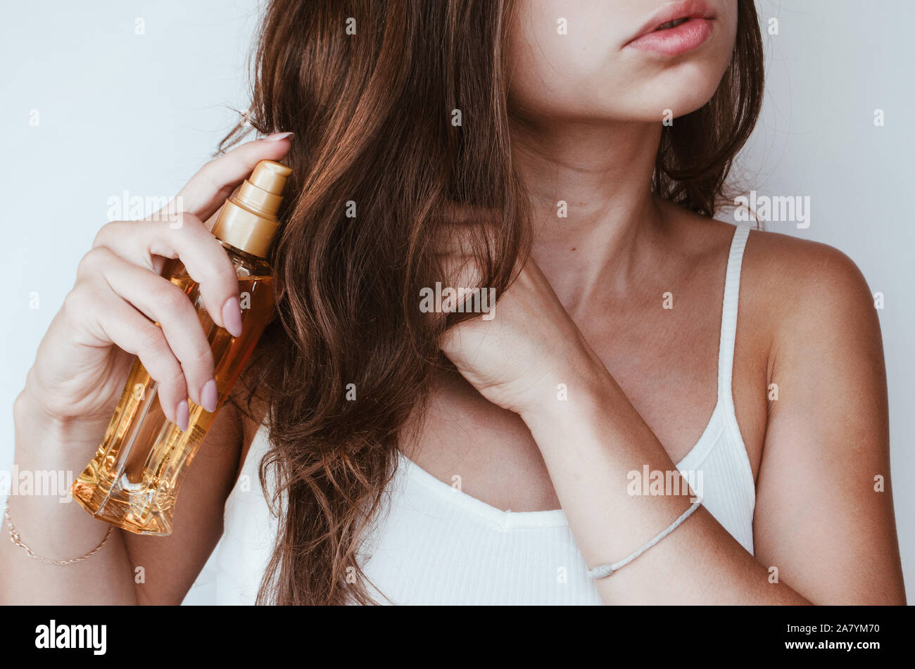 a woman with beautiful hair holds hair oil. The concept of hair care Stock Photo