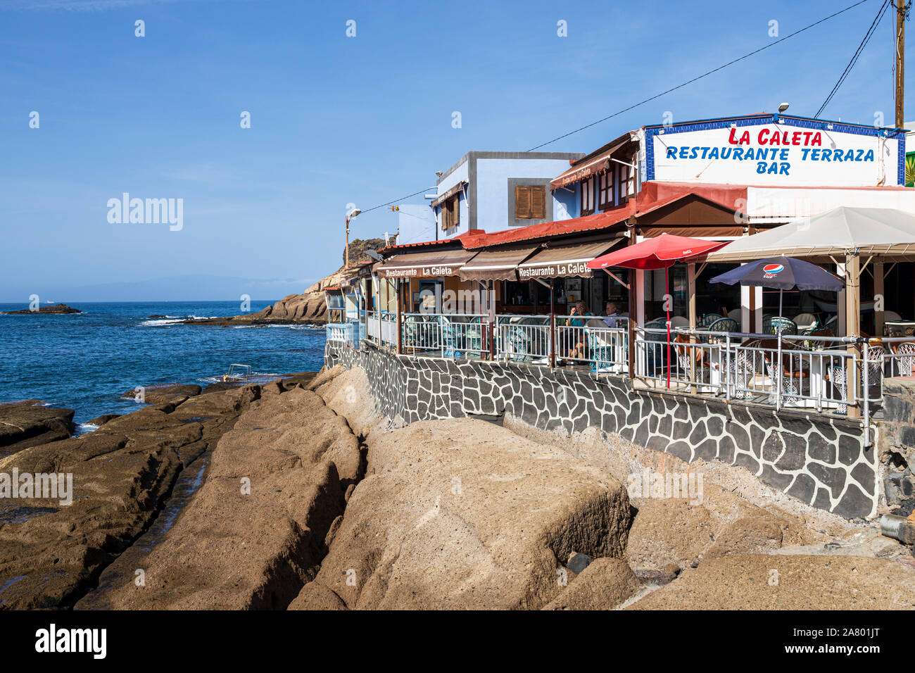 Restaurant, Terrace Bar, Cafe on the seafront in the early morning at La Caleta, Costa Adeje, Tenerife, Canary Islands, Spain Stock Photo