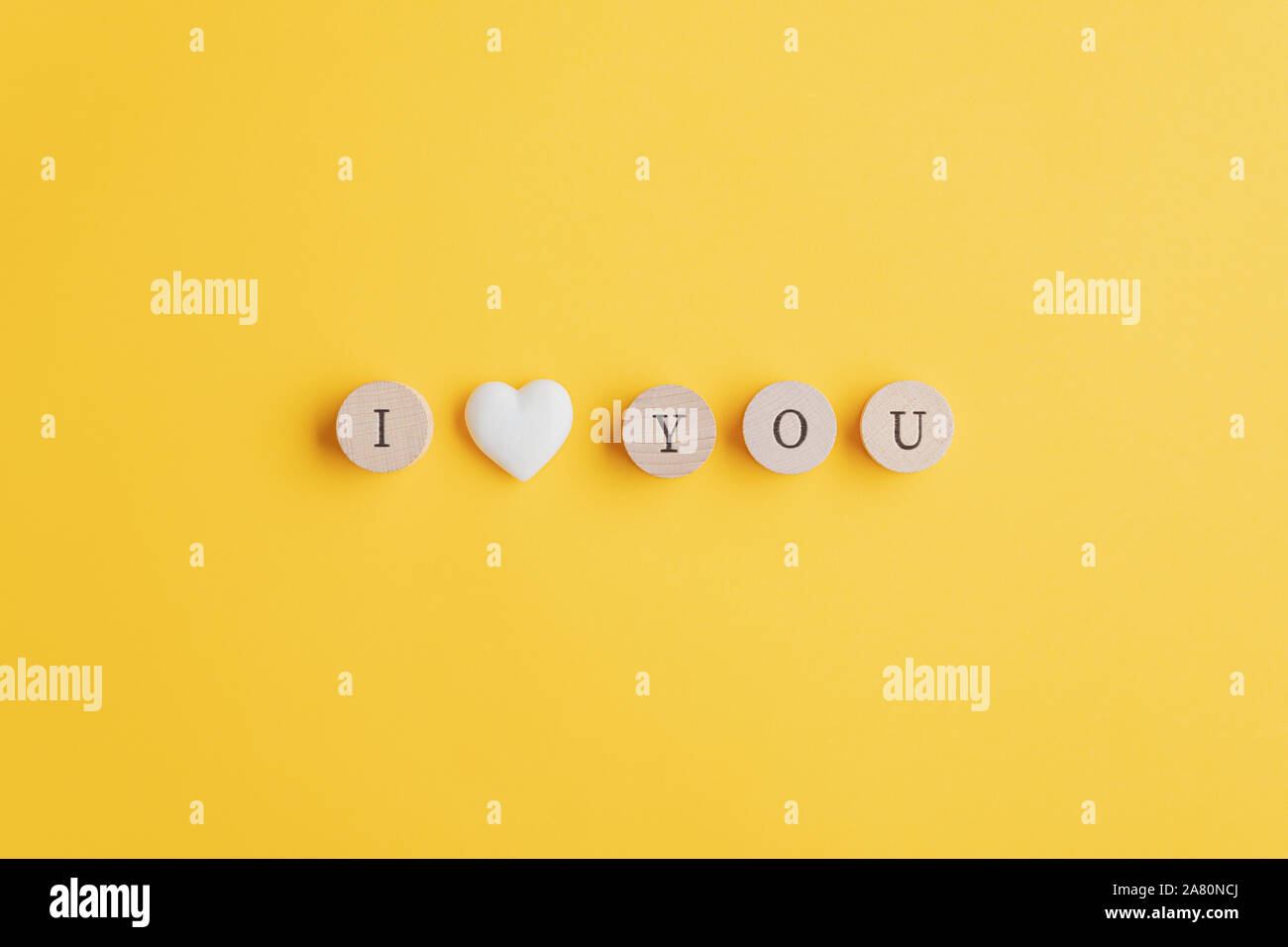 I love you sign spelled on wooden cut circles with a marble heart shape in between. Over yellow background with copy space. Stock Photo