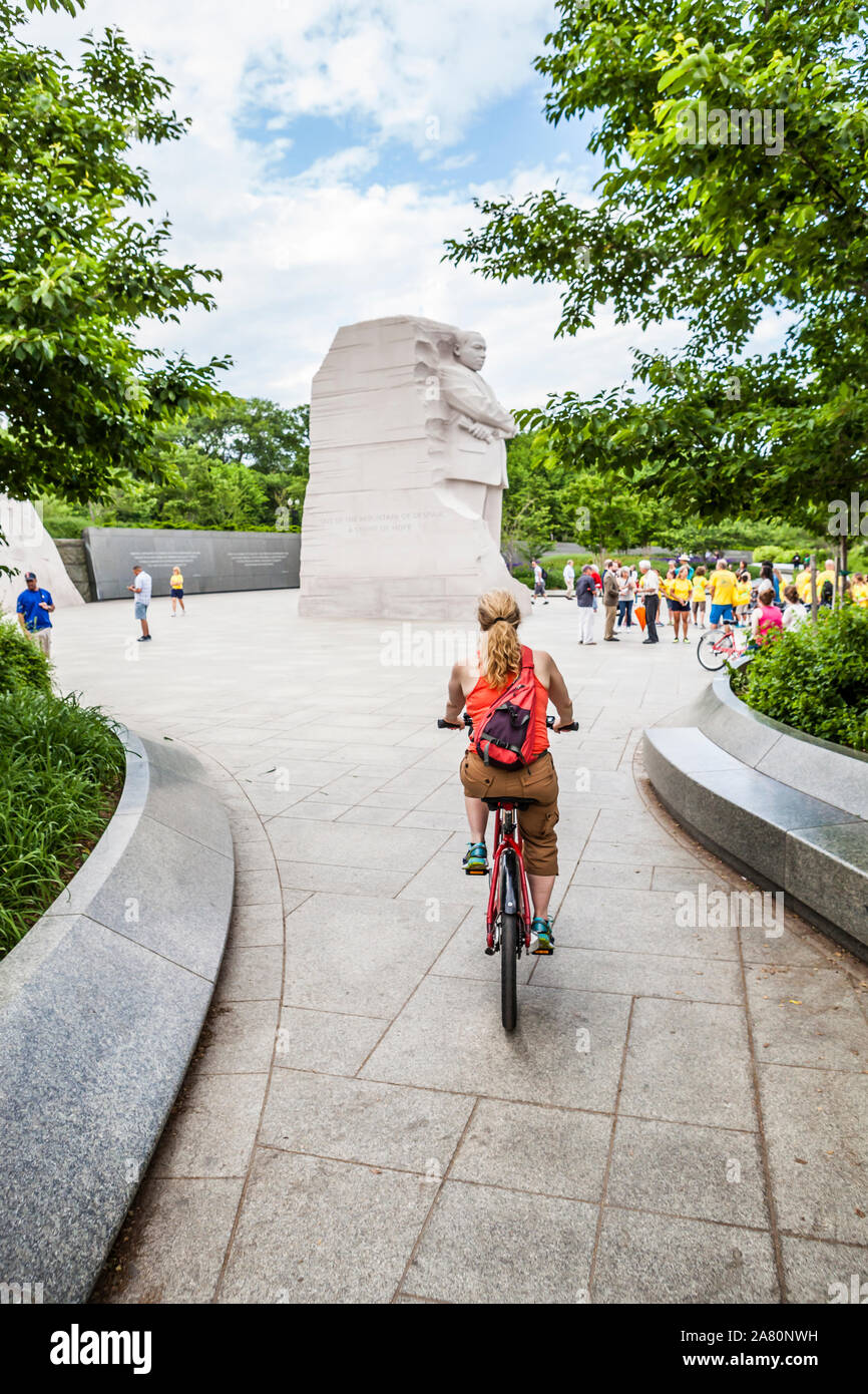 A woman approaches the Martin Luther King Jr memorial on a bike, Washington, D.C., USA. Stock Photo