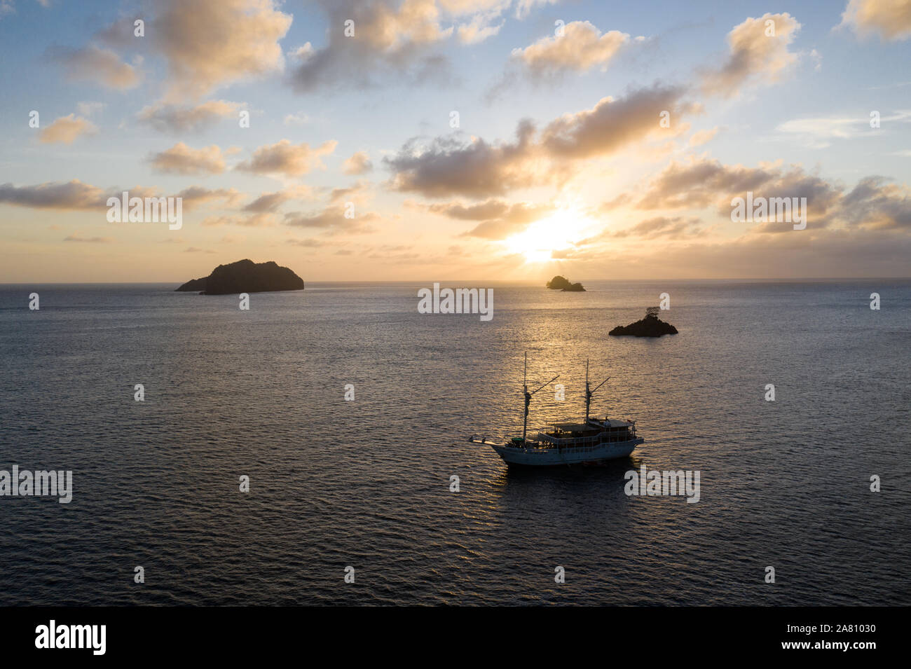 A peaceful sunset silhouettes limestone islands and a Pinisi schooner in Raja Ampat, Indonesia. This area harbors extraordinary marine biodiversity. Stock Photo