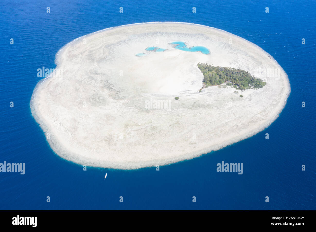 A Pinisi schooner drifts near the remote, tropical island of Midorang in the Ceram Sea. This area harbors extremely high marine biodiversity. Stock Photo