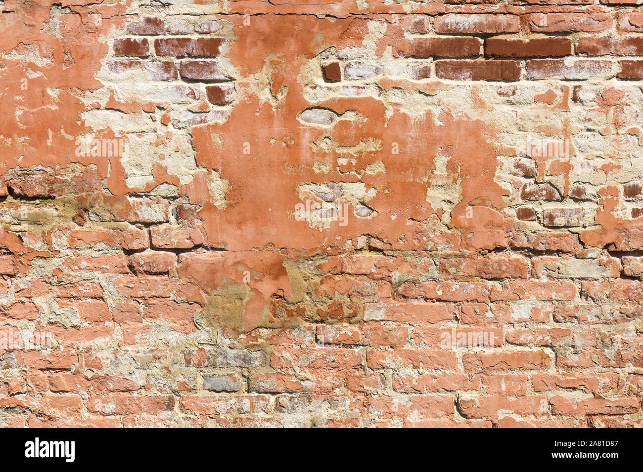 Brick wall pattern. Old wall built from the red bricks with remnants of plaster. Background texture. Stock Photo