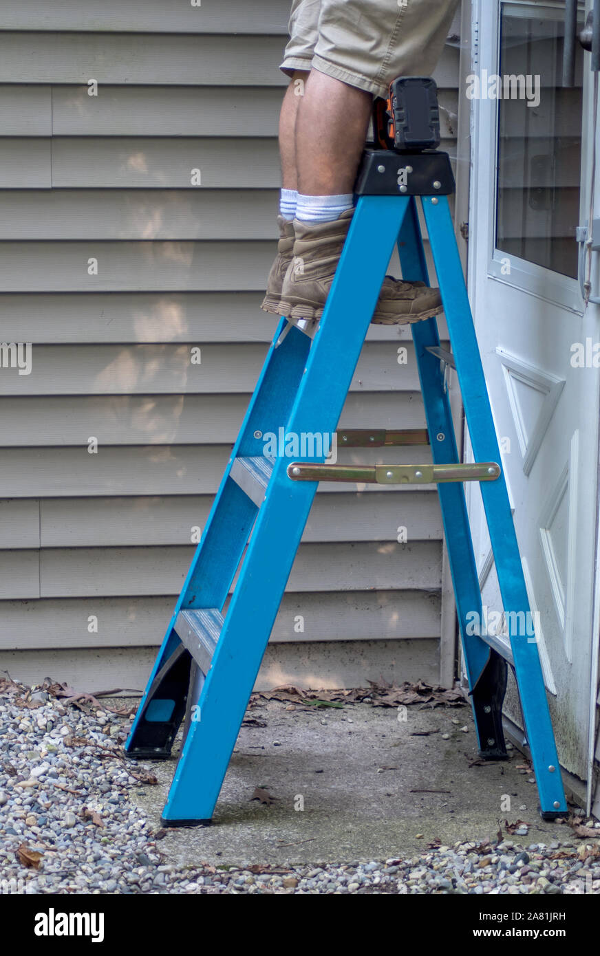 A worker stands on a step ladder as he works outdoors on the outside of a house Stock Photo