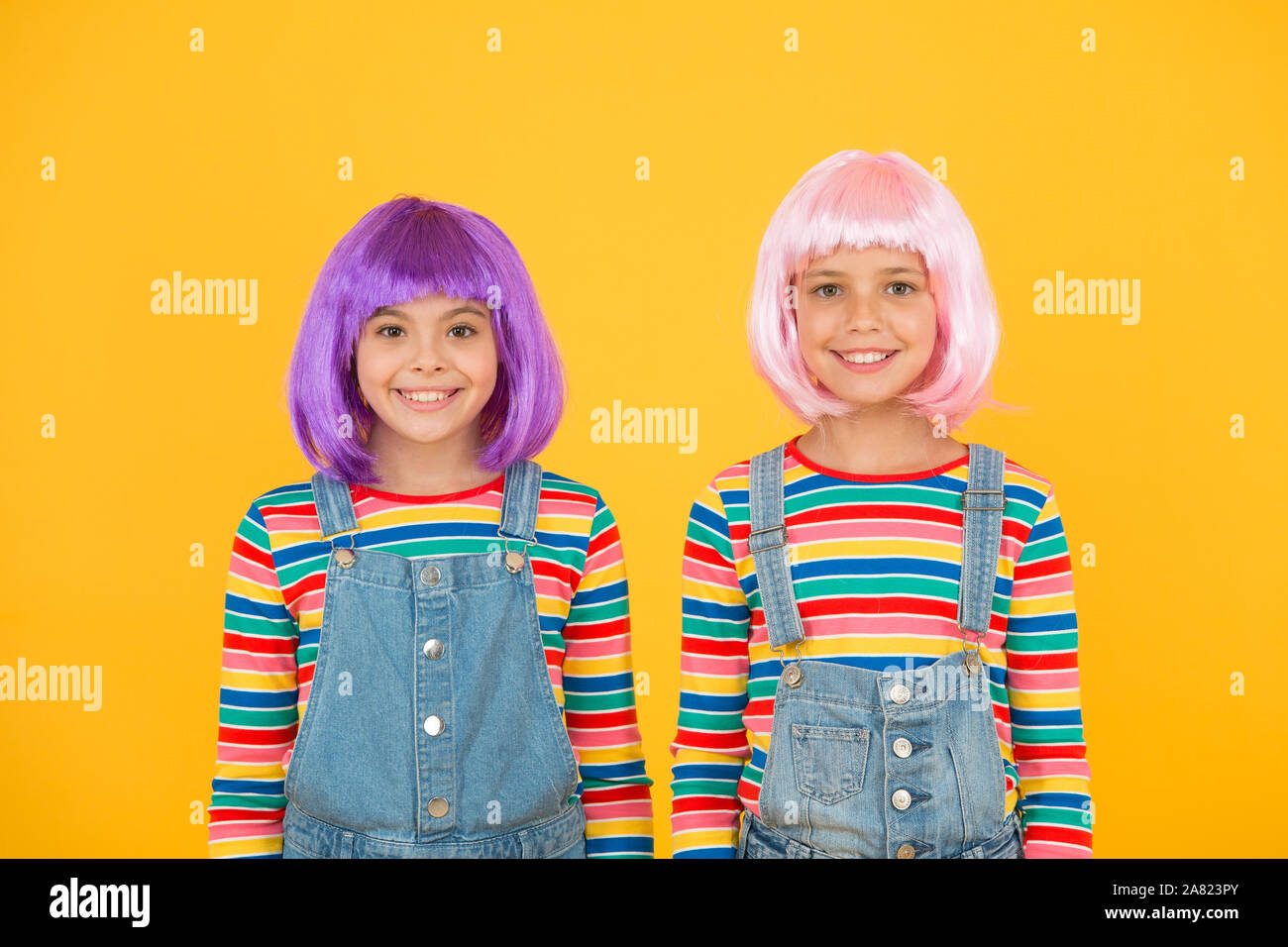 Ultra Modern Girls Happy Girls With Straight Short Hairstyle In Casual Style Cute Little Girls Smile With Fashion Look Small Girls Wear Colorful Hair Wigs Yellow Background Fashion And Beauty Stock Photo