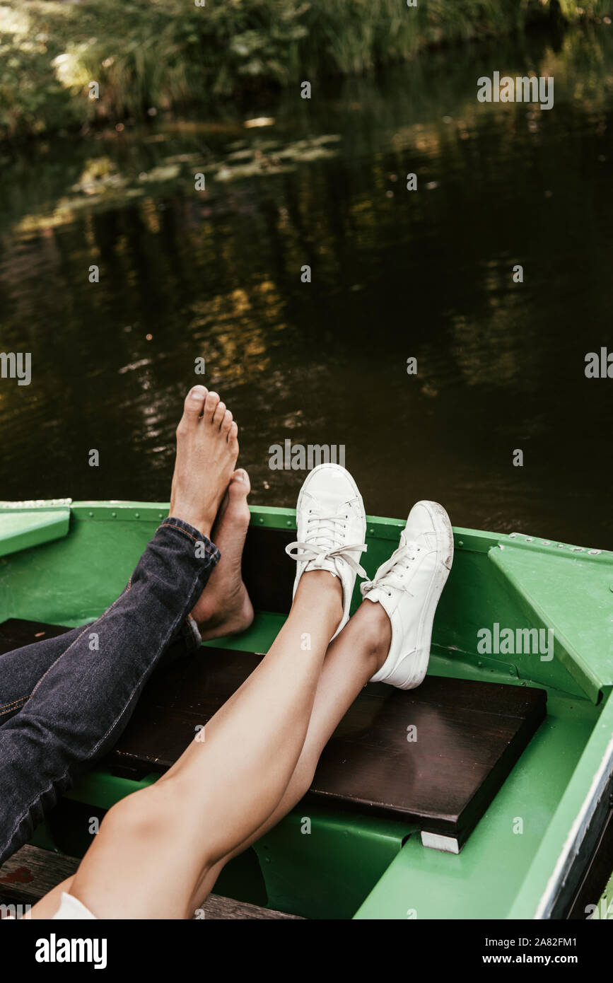 cropped view of barefoot man and girl in sneakers relaxing in boat on lake Stock Photo