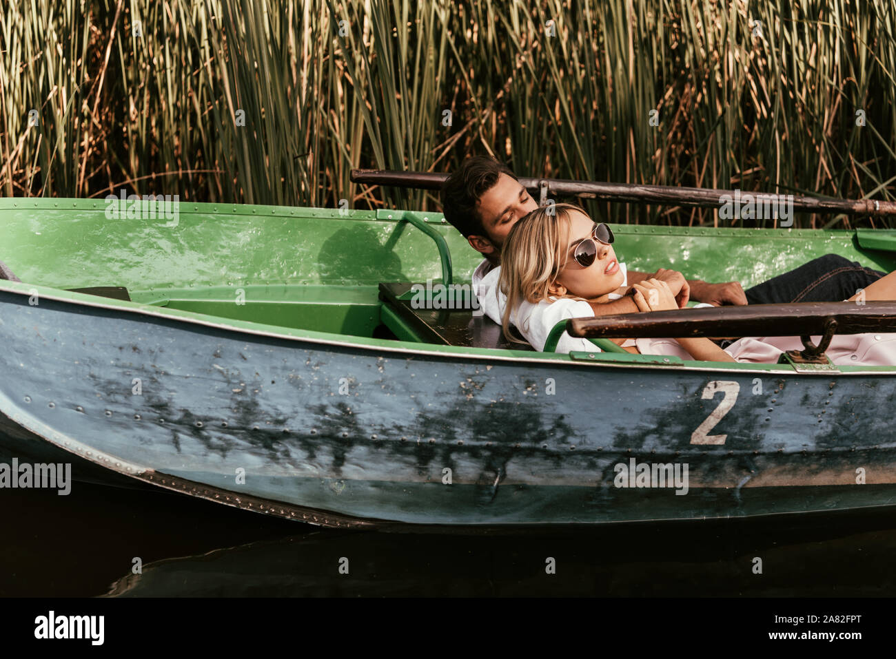 young couple relaxing in boat on river near thicket of sedge Stock Photo