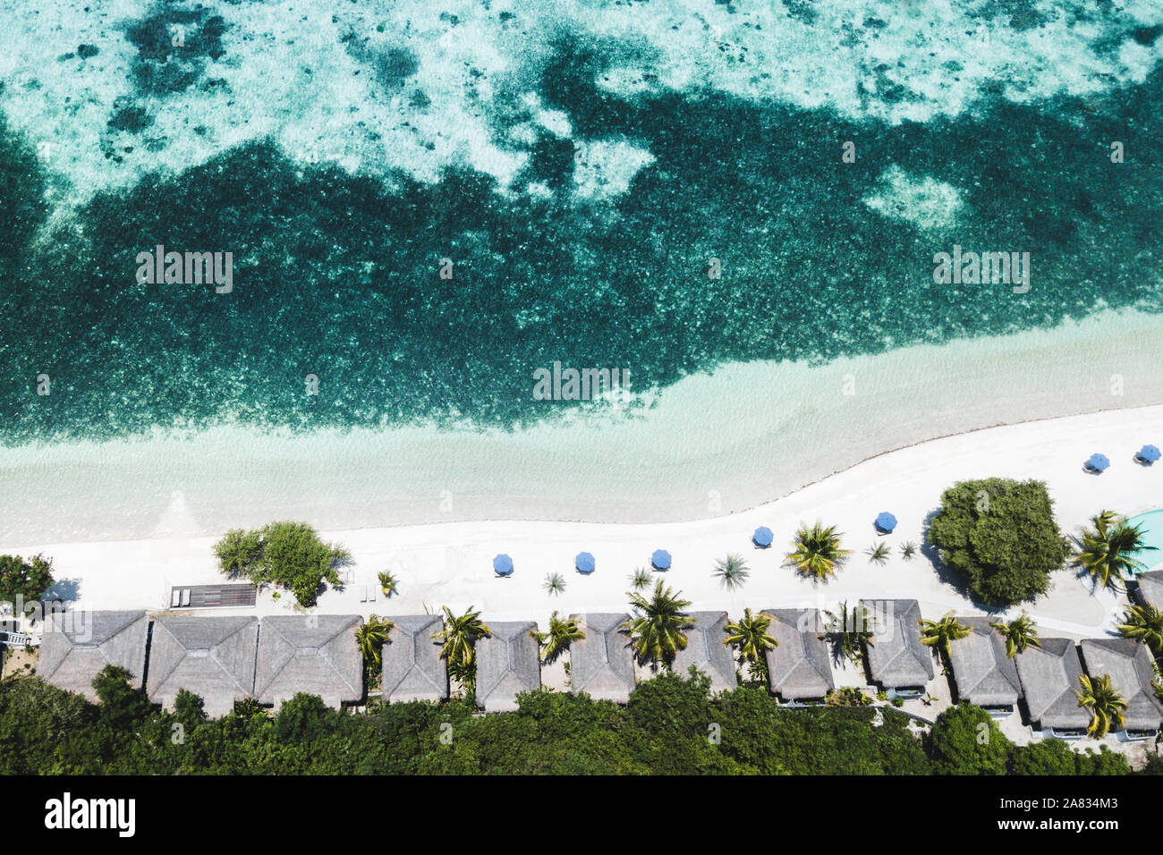 Aerial view of tropical white beach with blue umbrellas, coral reef and palms. Abstract drone shot from above. Travel and vacations concept. Stock Photo