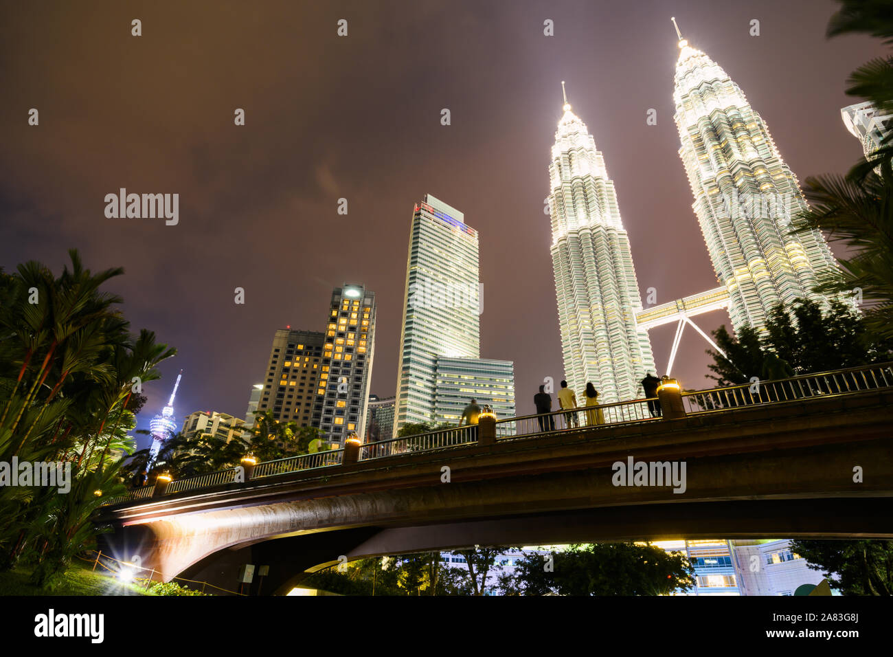 KL Tower and the Petronas Twin Tower illuminated at dusk. People enjoying the view from a bridge in KLCC Park Stock Photo