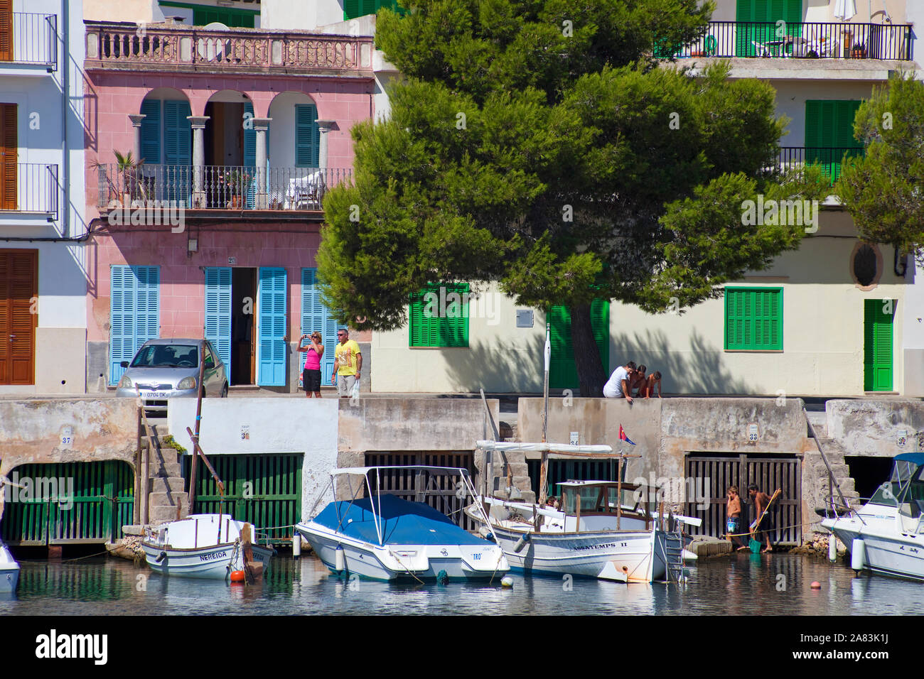 Boat garages under former fishing houses, historic harbour of Porto Colom, Mallorca, Balearic islands, Spain Stock Photo