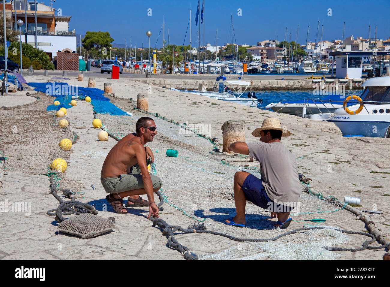 Fishermen repairing their nets at the harbour of Porto Colom, Mallorca, Balearic islands, Spain Stock Photo