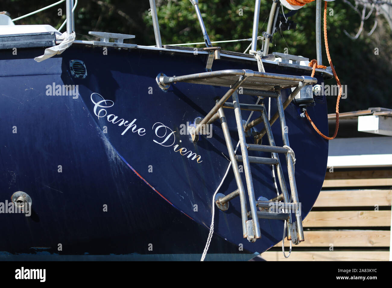 Latin words carpe diem translated as meaning 'seize the day'. The name of a boat seen in dry dock in the port of Numana on the Adriatic coast in Italy Stock Photo