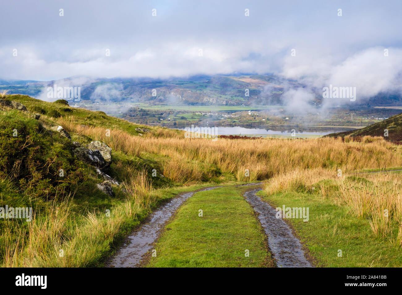 Farm track in Rhinog hills above Afon Dwyryd river estuary with low cloud on mountains of northern Snowdonia. Eisingrug Harlech Gwynedd Wales UK Stock Photo