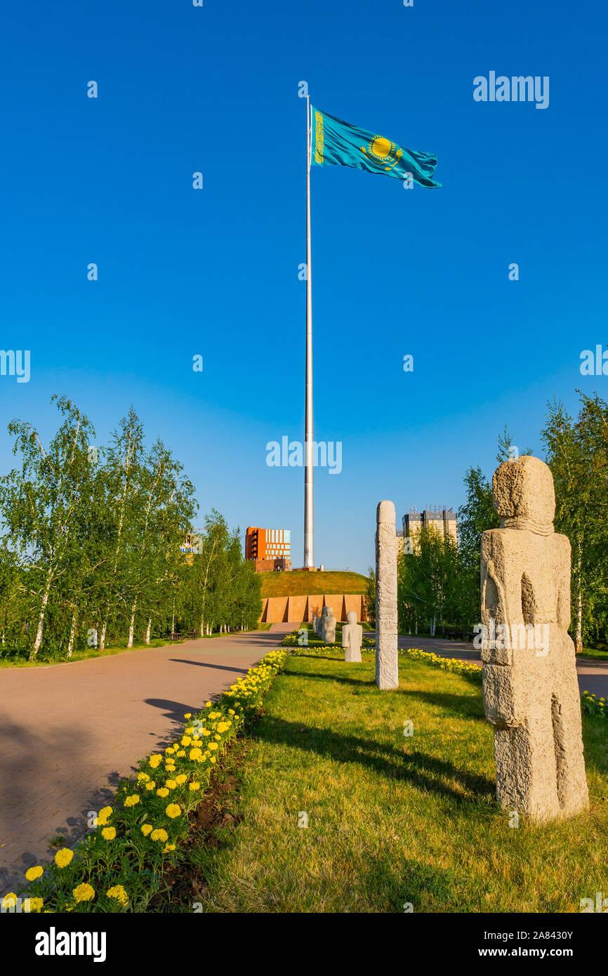 Nur-Sultan Astana Central City Tsentralnyy Gorodskoy Park View of Waving Kazakhstan Flag and Balbal Sculpture on a Sunny Blue Sky Day Stock Photo