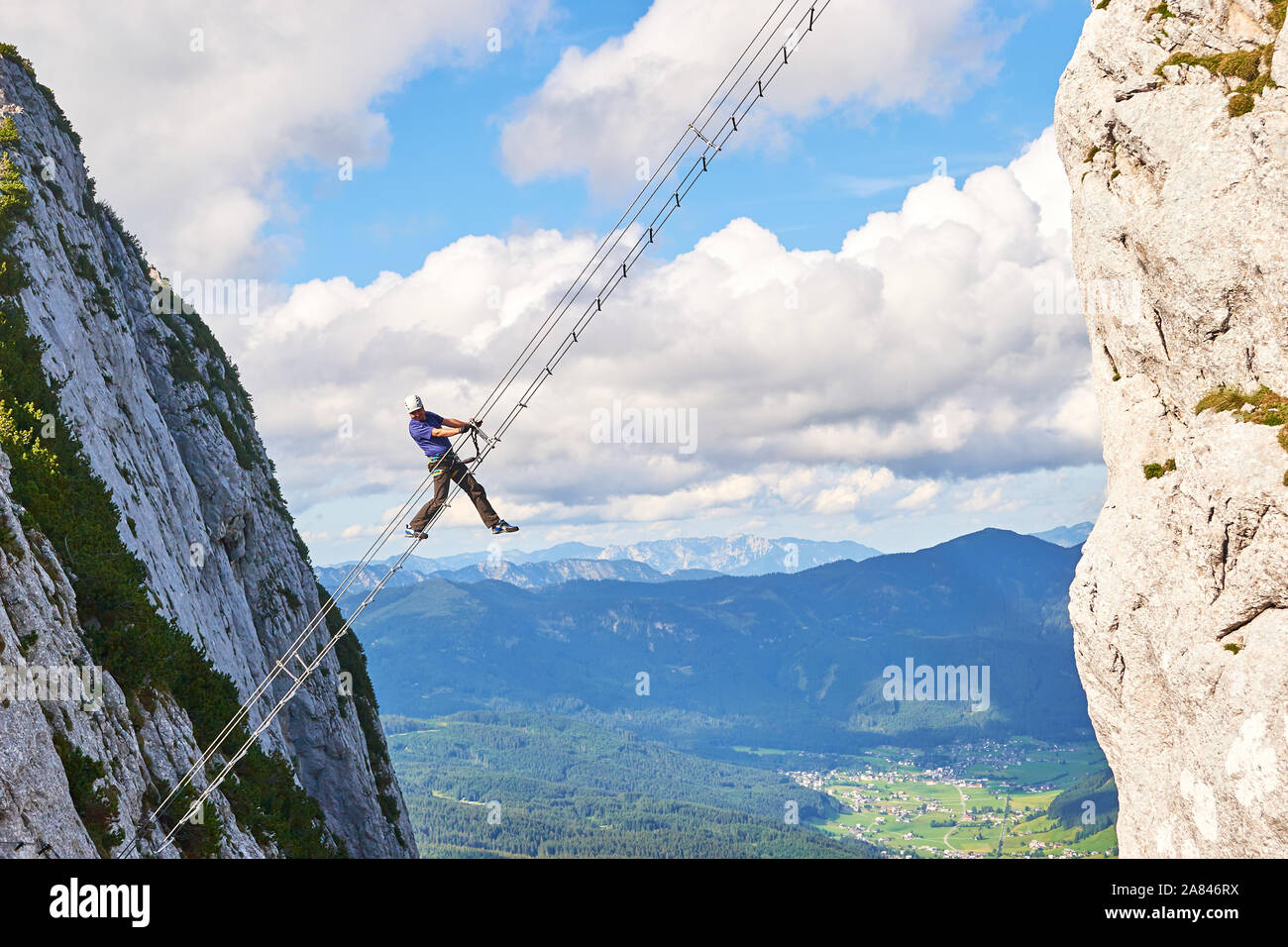 Man posing on Donnerkogel Intersport via ferrata (klettersteig) ladder, with his leg  hanging out, on a bright sunny day. Stock Photo