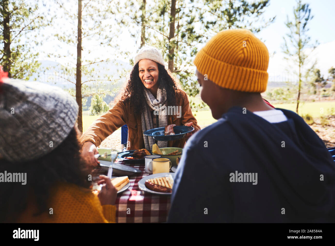 Happy mother and kids eating at campsite Stock Photo