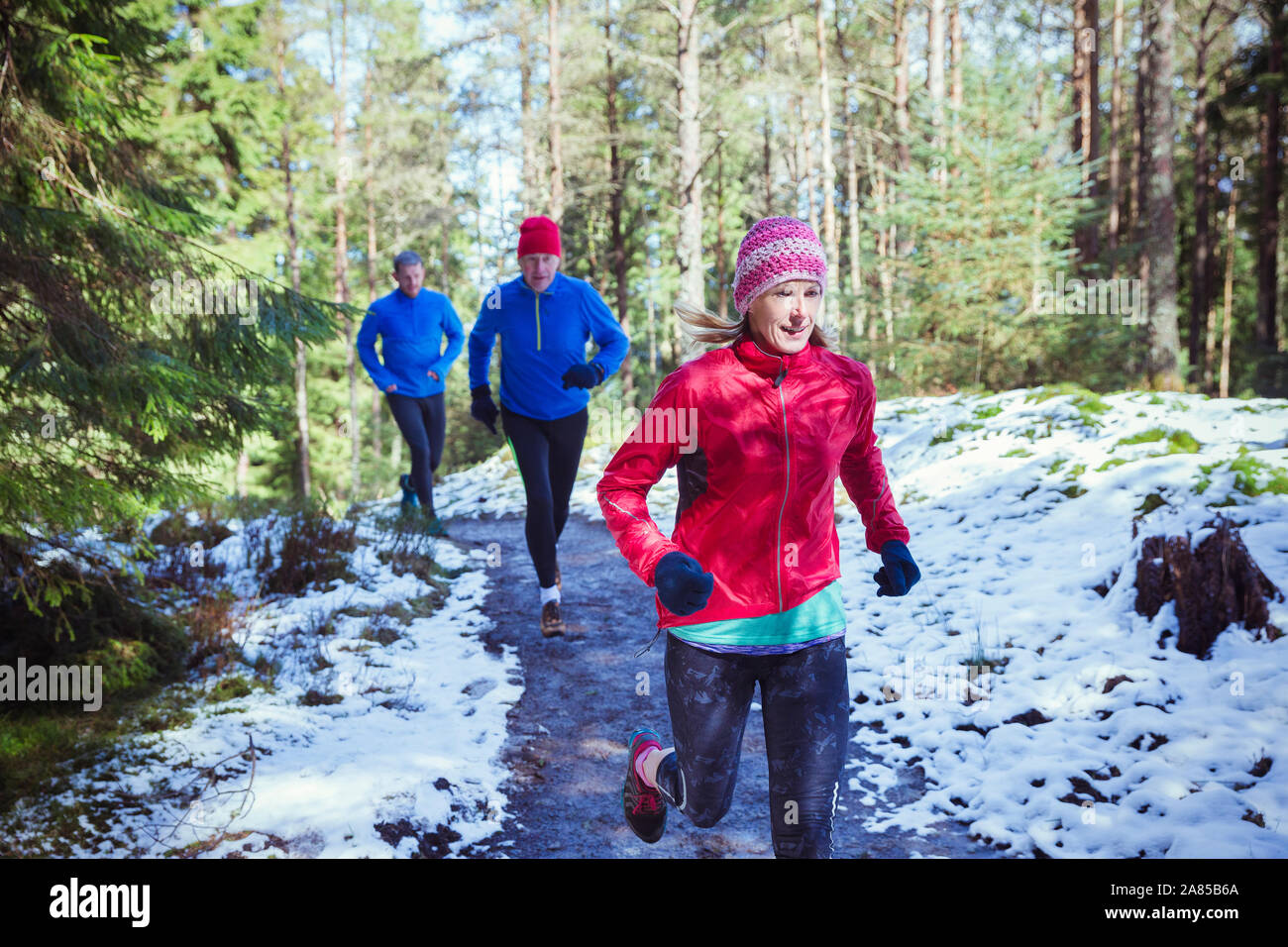 Family jogging on trail in snowy woods Stock Photo