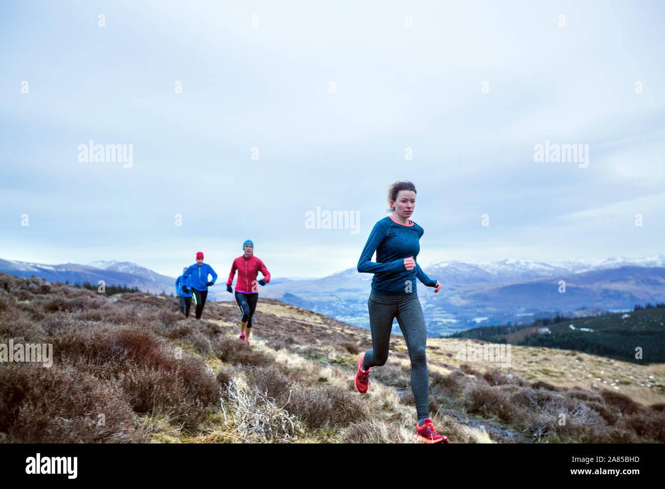 Friends jogging on trail in remote mountains Stock Photo