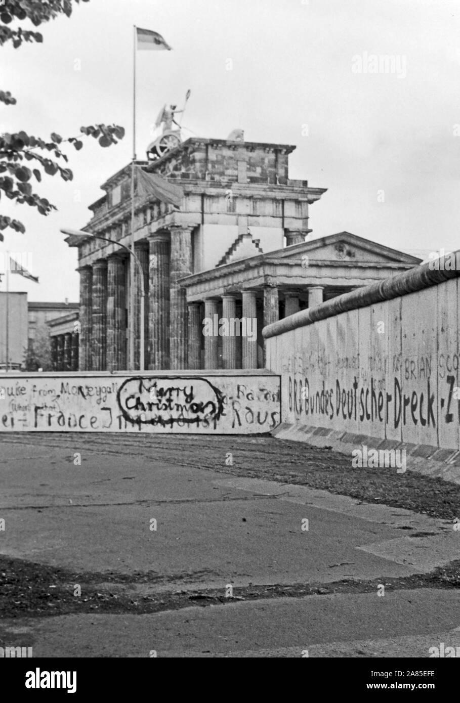 Weihnachtswünsche aufgesprüht auf die Mauer in Berlin am Brandenburger Tor, Deutschland 1984. Season's greetings sprayed on the Berlin wall near Brandenburg gate, Germany 1984. Stock Photo