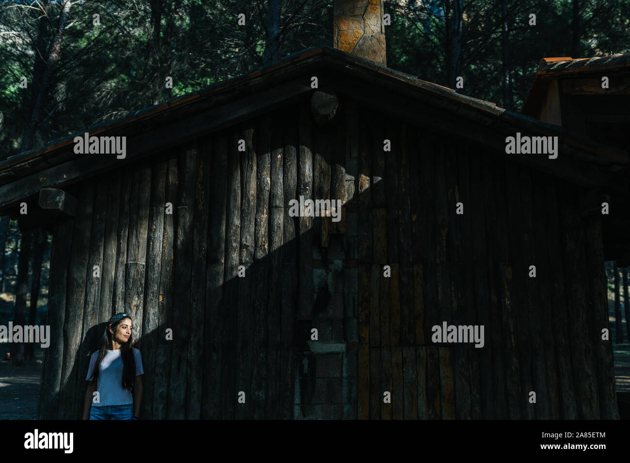 Woman in the countryside alone, next to a wooden cabin, during a spri Stock Photo