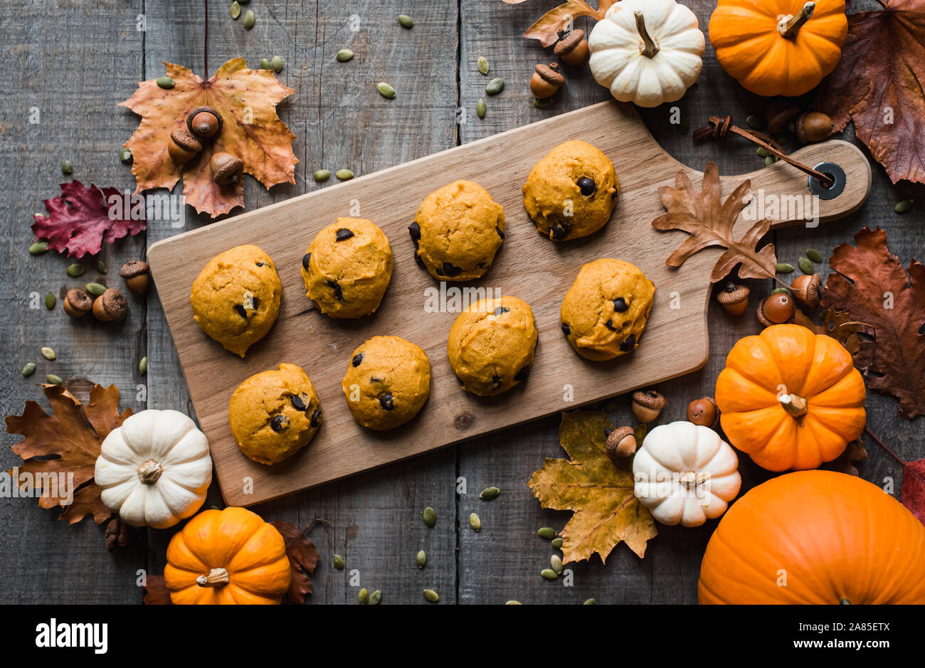 Overhead view of pumpkin chocolate chip cookies on wooden table. Stock Photo