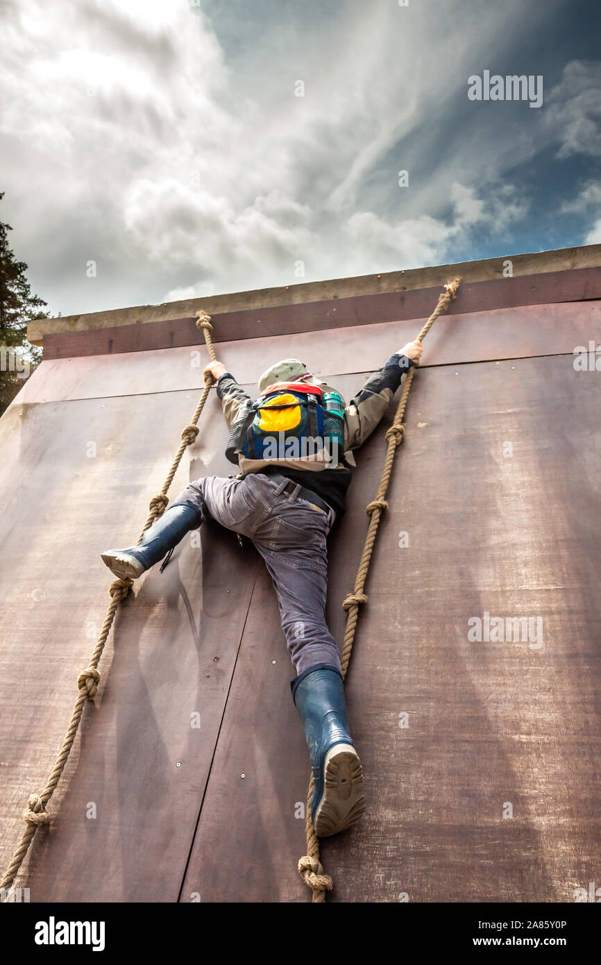 Young boy in wellys climbing up a wall with ropes. Stock Photo