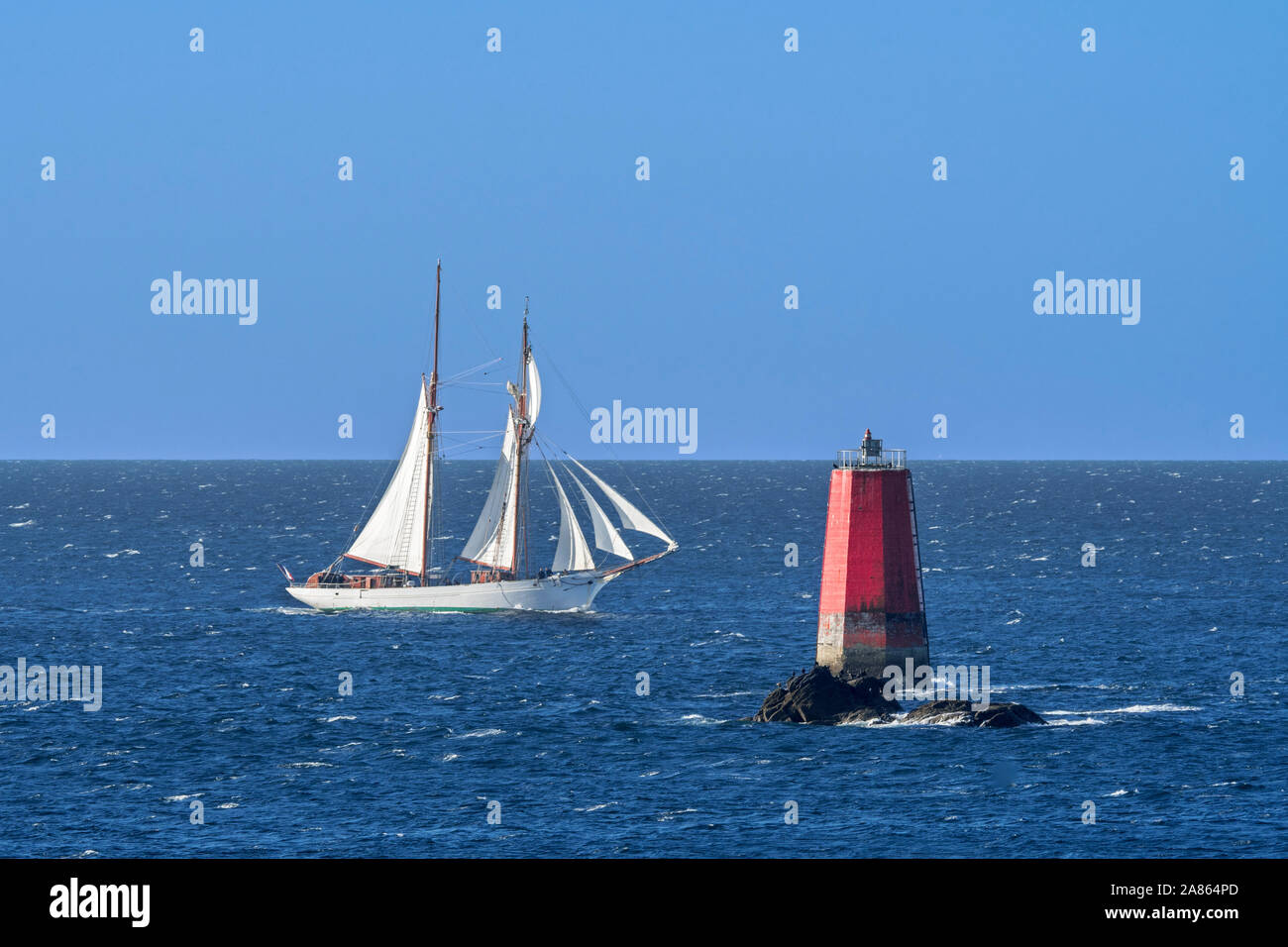 Sailing ship passing red sea mark / seamark / navigation mark on the shallows Les Vieux Moines at Pointe Saint-Mathieu, Finistère, Brittany, France Stock Photo