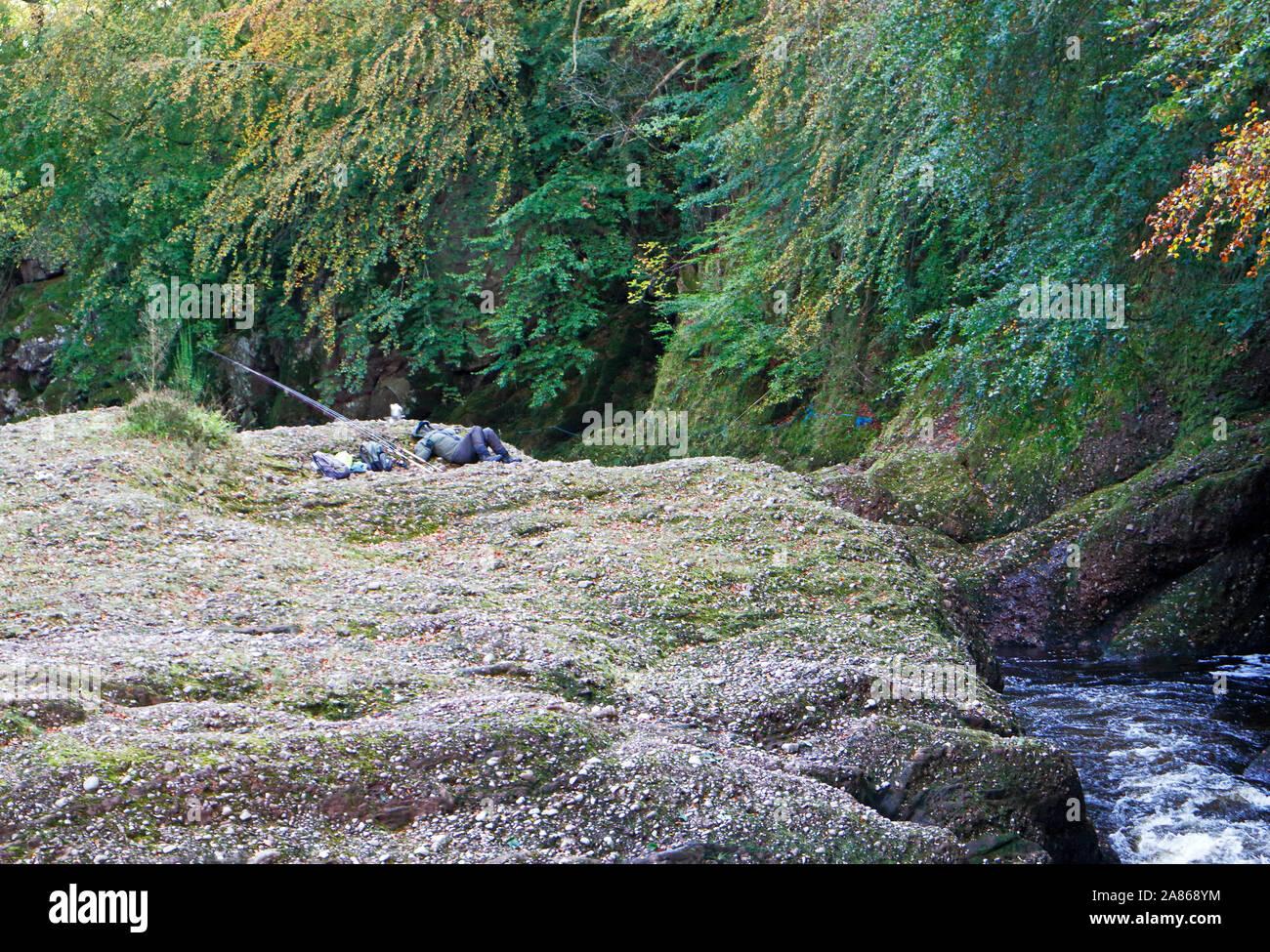 An salmon fishing angler resting on rocks by the River North Esk near Edzell, Angus, Scotland, United Kingdom, Europe. Stock Photo