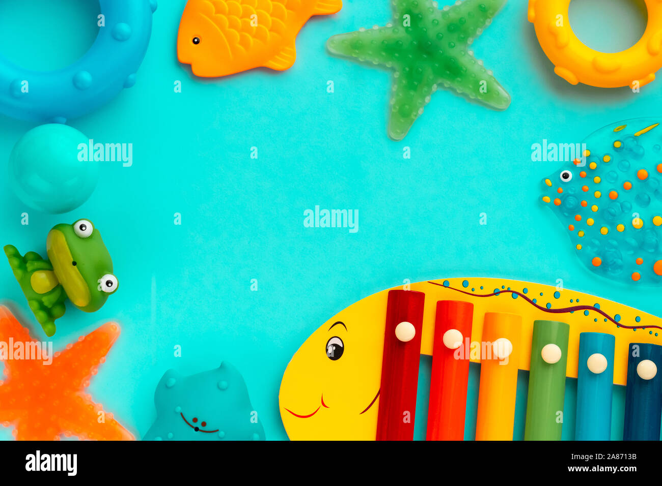 Top view on children's educational and music games, frame from multicolored kids toys on light blue paper background. Circles, fish, frog, starfish, xylophone. Sea, ocean concept. Flat lay, copy space for text. Stock Photo