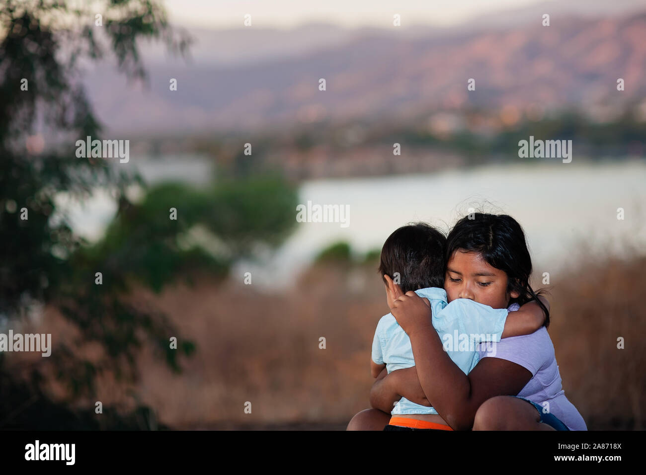 Brother and sister separated from parents are hugging each other in a foreign country, across a river. Stock Photo