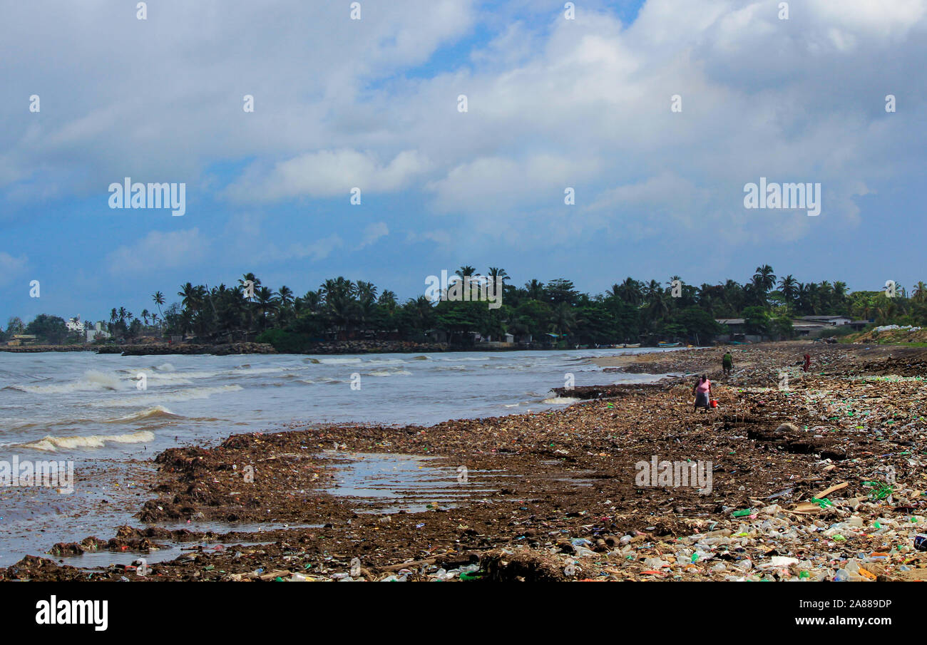 Sea Pollution: Garbage dumped in the Sri Lankan Sea near Colombo. women collects plastic things in a pile of garbage brought by the surf from the sea Stock Photo