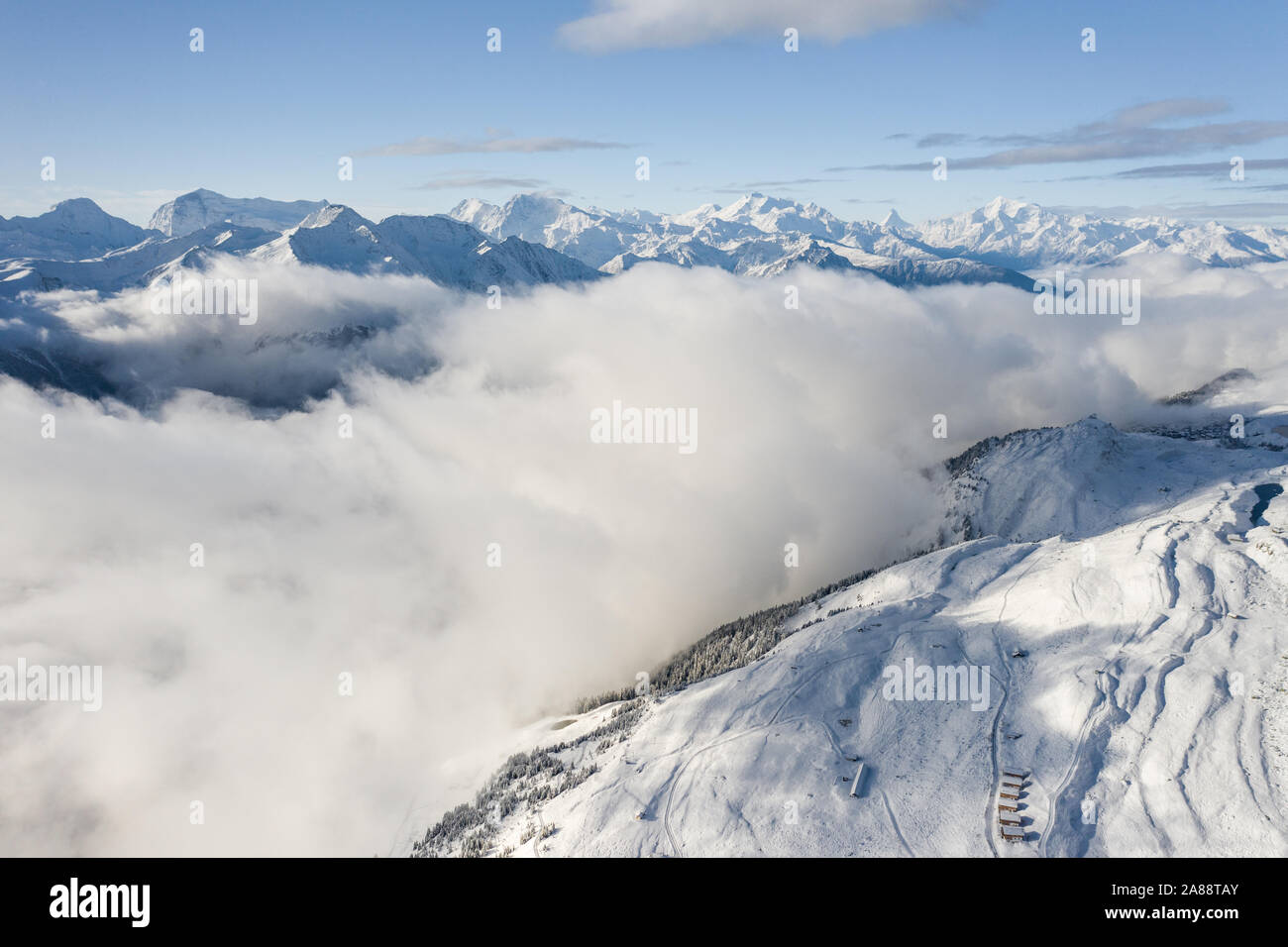 Aerial view of a forest covered with fresh snow and clouds in the Aletsch Arena area. Switzerland in the fall Stock Photo