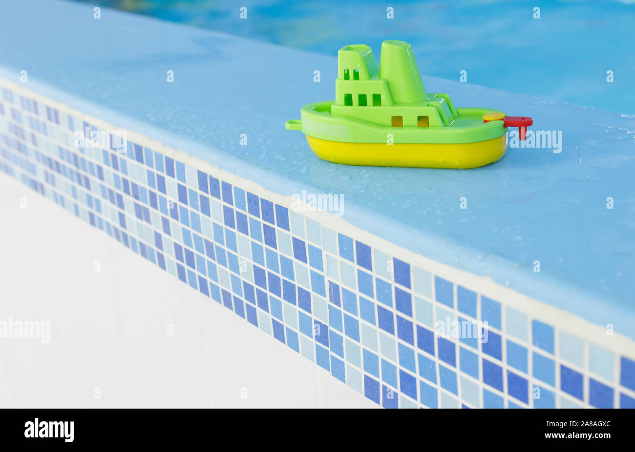 green boat on the side of the pool. Empty indoors public swimming pool. children center Stock Photo