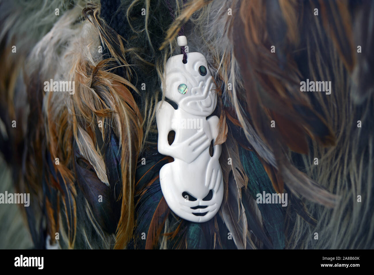 A Traditional Maori Bone Carving Nestled In A Feather Cloak New Zealand Stock Photo Alamy