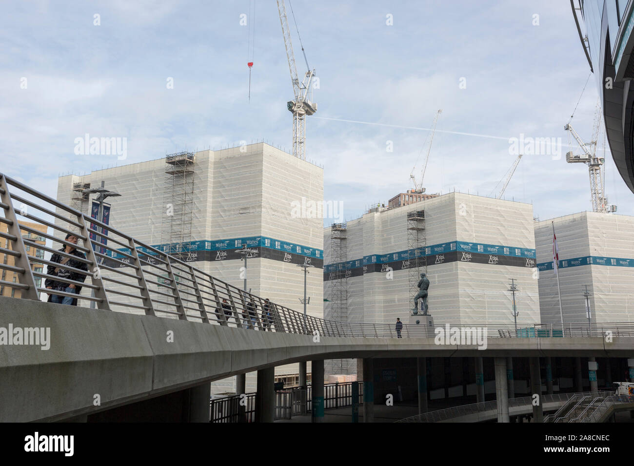 A landscape of regeneration around the Wembley Stadium arena where new properties are under construction tower over the statue of English football's most loved player, Bobby Moore, on 6th November 2019, in Wembley, London, England. Sir Bobby Moore captained England to its World Cup victory against Germany at the old Wembley stadium in 1966. Stock Photo