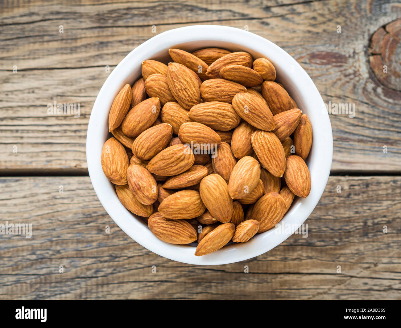 Top view of white cups, bowls with a handful of pecans, almonds on a wooden background Stock Photo