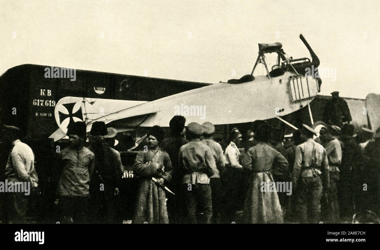 """Captured German plane, Russia, First World War, 1914-1918, (c1920). 'Brought down behind the Russian Lines: captured German Albatross machine being dispatched by rail to a repair-shop'. Russian soldiers with an Albatros D.III biplane fighter aircraft of the Imperial German Army Air Service (Luftstreitkräfte). From """"The Great World War: A History"""", Volume V, edited by Frank A Mumby. [The Gresham Publishing Company Ltd, London, c1920] Stock Photo"""