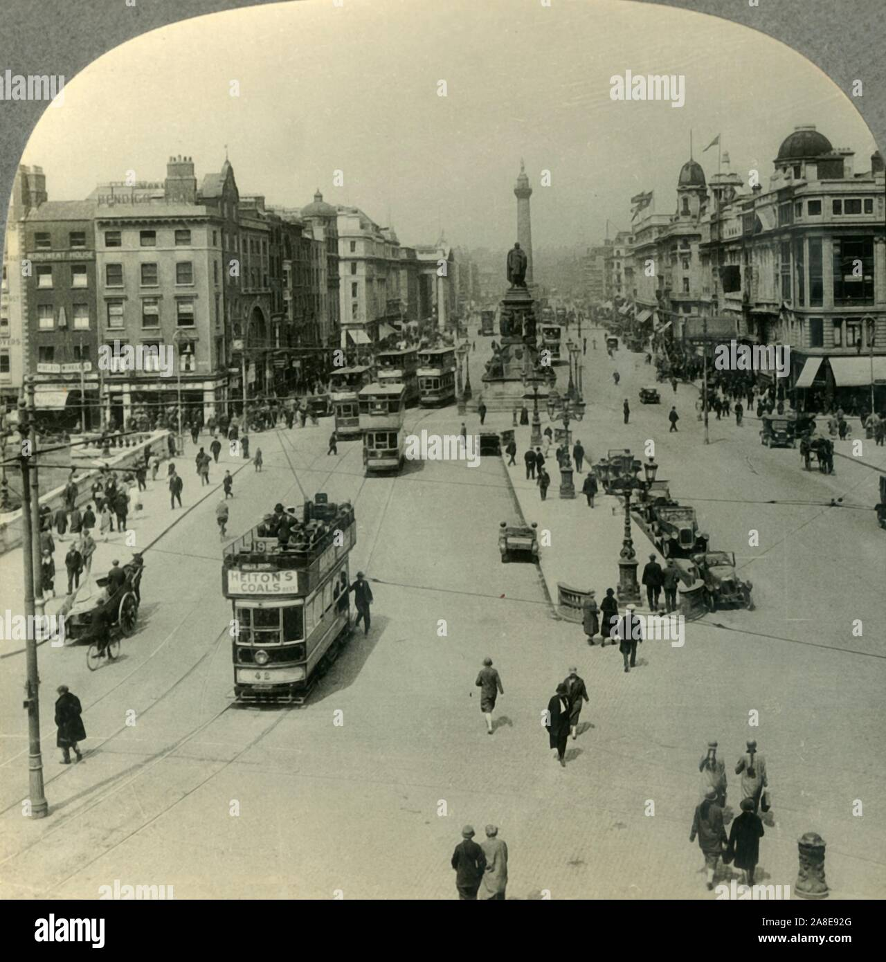 """'The O'Connell Monument and the Nelson Pillar, O'Connell Street, Dublin, Ireland', c1930s. Memorial to Daniel O'Connell by John Henry Foley and Nelson's Pillar  damaged by explosives in 1966 on O'Connell Street in Dublin.  From """"Tour of the World"""". [Keystone View Company, Meadville, Pa., New York, Chicago, London] Stock Photo"""