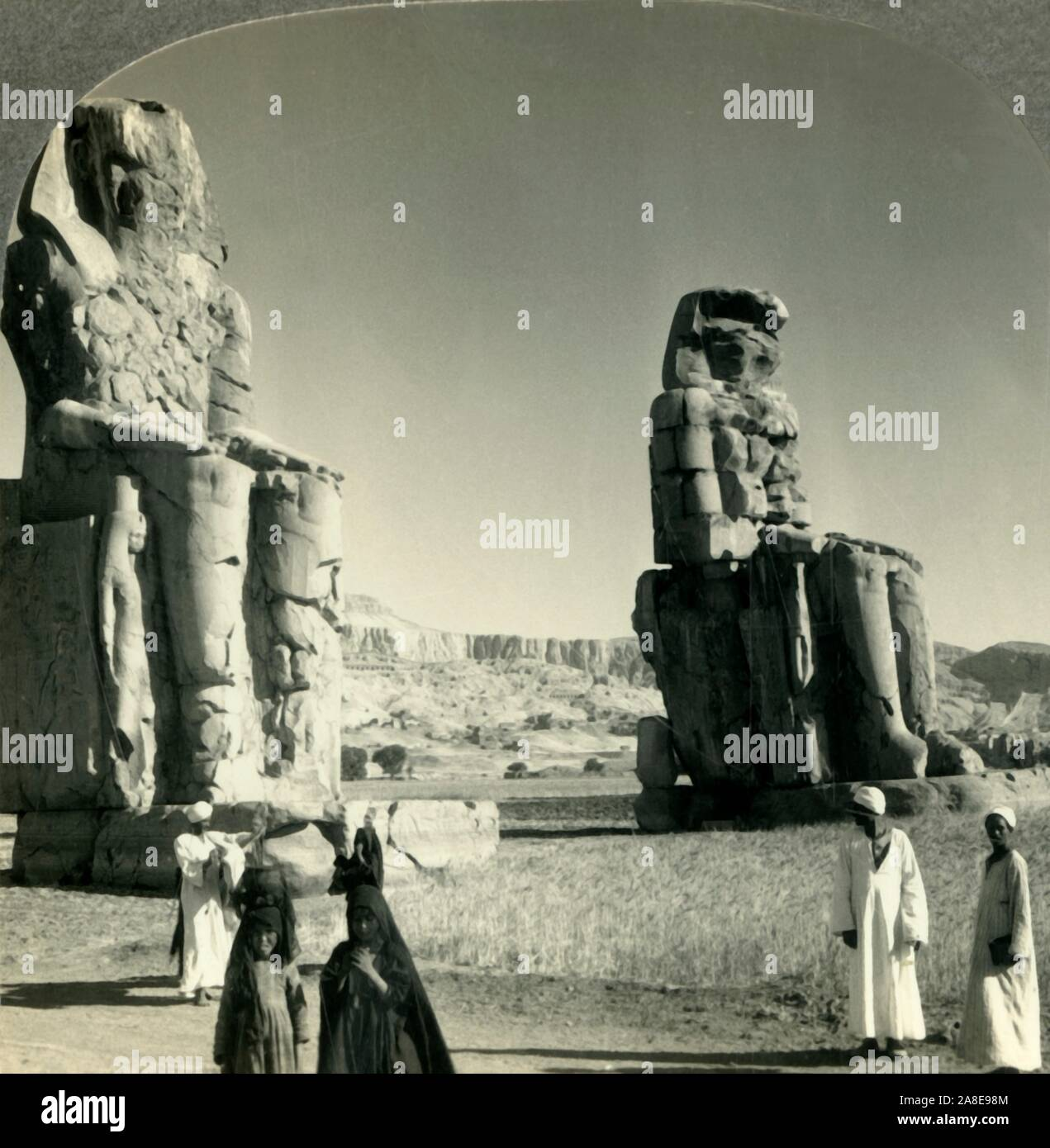 """'Colossal """"Memnon"""" Statues at Thebes - the Farther One Used to Emit a Cry at Sunrise, Egypt', c1930s. Colossi of Memnon,  statues of the Pharaoh Amenhotep III, who reigned Egypt during the Dynasty XVIII. From """"Tour of the World"""". [Keystone View Company, Meadville, Pa., New York, Chicago, London] Stock Photo"""